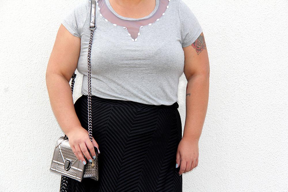 look plus size com bolsa prateada, blusa mescla e saia preta, moda plus size