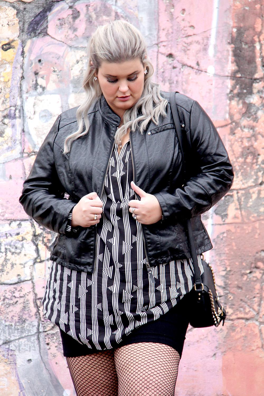 Look do dia plus size com jaqueta de couro sintético, meia arrastão, bota preta e chemise com estampa geométrica!